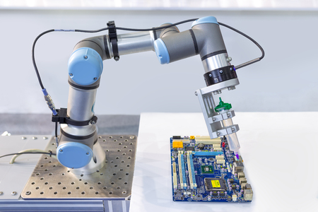 Industrial robot installing a computer chip at production line in factory, Controller of robotic arm.