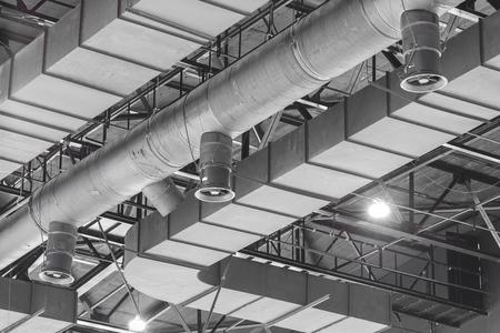 HVAC Duct Cleaning, tubos de ventilación en material de aislamiento de plata que cuelga del techo dentro del nuevo edificio. Foto de archivo