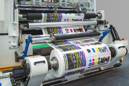 Impresora offset grande o revista corriendo un largo rollo de papel en la línea de producción de la impresora industrial de la máquina. Foto de archivo