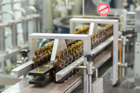 Sterile bottles on the production line conveyor of the pharmaceutical industry. Machine for iquid drugs glassware bottling. Stock Photo