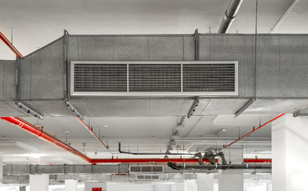 Industrial air duct ventilation equipment and pipe systems installed on industrial building ceiling. Stock Photo