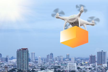 Drones flying through the air in sunset sky with a cardboard box package carrying clamped to send for customer. Futuristic delivery drone concept. Stock Photo