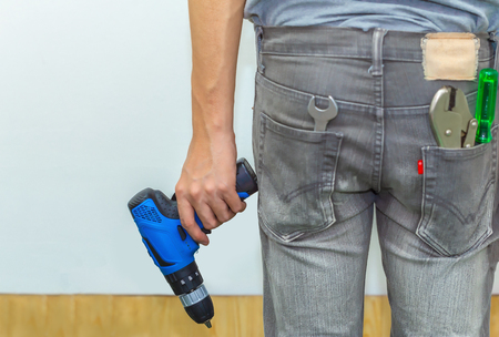 Craftsman or carpenter holding electric drill in hands Manual job, DIY inspiration, improvement, fix shop, industrial education, professional career concept.