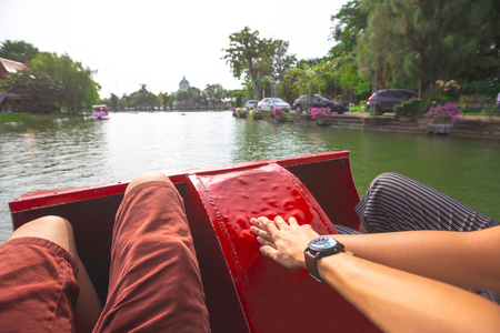 Young lovers having fun and holding hands on pedal boat or water cycle on hot summer day in public park.
