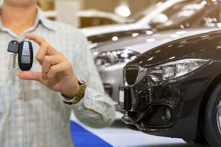 Salesman or dealer offering car keys to new owner in showroom, buy or rent concept.
