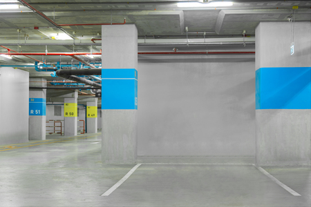 Parking garage interior, neon lights in dark industrial building, modern public construction
