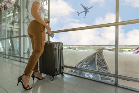 Woman tourist standing with luggage watching sunset at airport window while waiting at boarding gate before departure at lounge. Travel lifestyle.