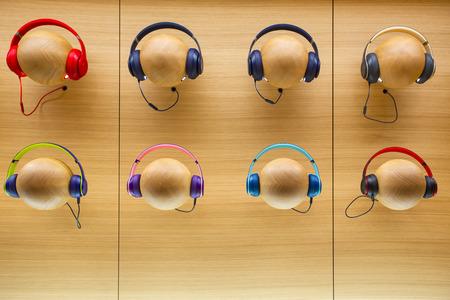 Colourful stylish headphones on wooden background.