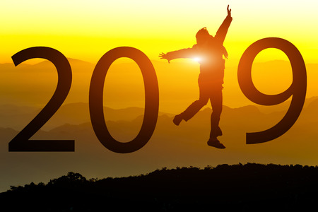 Silhouette of freedom happy young woman jumping on on the hill with New year 2019 concept in sunset background.