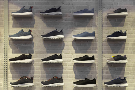 Shop display of unbranded modern new stylish sneakers running shoes for men on brick wall background texture.