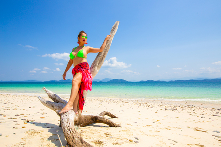 Portrait of young woman wearing a pink sarong and bikini on the tropical beach. Blue sea in the background. Summer vacation concept.