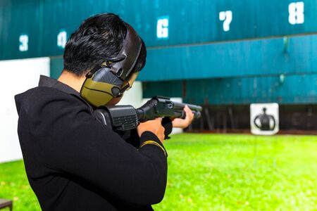 Eine Soldatin mit Strafverfolgungsbehörden zielt mit einer langen Schrotflinte auf Kampfkünste zur Selbstverteidigung in einem Notfall. Schießwaffe mit zwei Händen im Schießstand der Akademie. Standard-Bild