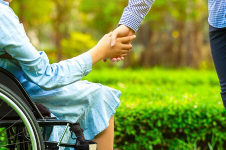 Young woman in wheelchair holding hands with caretaker man in public park. 版權商用圖片