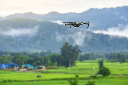 Drone copter flying with digital camera in mountains.