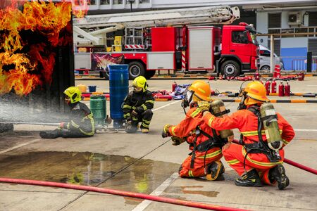 Brave firefighter using extinguisher and water from hose for fire fighting, Firefighter training with protective wear spraying high pressure water to fire. 版權商用圖片