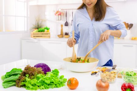 Young Woman Cooking in the kitchen. Healthy Food - Vegetable Salad. Diet. Dieting Concept. Healthy Lifestyle. Cooking At Home. Prepare Food. 版權商用圖片