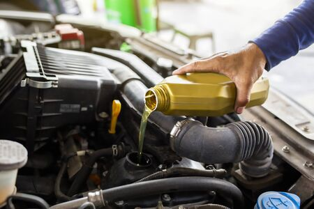 Car mechanic replacing and pouring fresh oil into engine at maintenance repair service station.