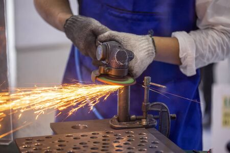 Roofer using a angle grinder to cut a metal.