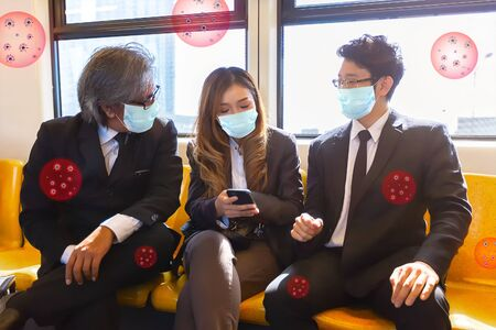 Business company wearing healthy face mask to protect corona virus (Covid-19) on skytrain Transit System Public while going to work in the morning.