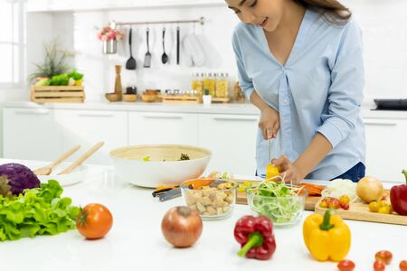 Young Woman Cooking in the kitchen. Healthy Food - Vegetable Salad Diet. Healthy Lifestyle. Cooking delicious food during the COVID-19 self-quarantine 14 days. Stay at home concept. Zdjęcie Seryjne