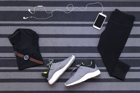 Top view of running shoes, womens clothes, pants tights, smartphone run application isolated on grey carpet. Zdjęcie Seryjne - 148794897