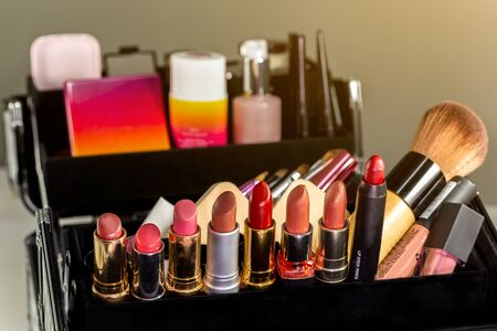 Make up case containing colorful eyeshadows, lipsticks, lip glosses, blushes and nail polishes. Zdjęcie Seryjne - 147160617