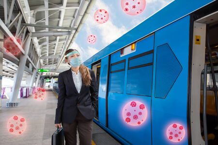 Young Asian Businesswoman  wearing face mask and face shield waiting for the train to arrive at skytrain station. New normal after Coronavirus (COVID-19) pandemic concept.