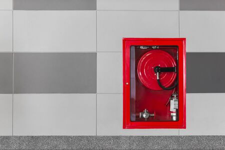 Hydrant with water hoses and fire extinguish equipment on the wall in an corridor. Zdjęcie Seryjne - 148953232