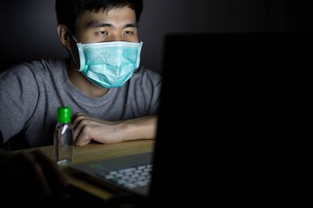 Asian man work from home and wear a protective medical mask. Clean his hands with sanitizer alcohol gel to prevent Coronavirus (CoVID-19) outbreak.