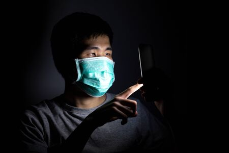 Asian man using smart phone work from home and wear a protective medical mask to prevent Coronavirus (CoVID-19) outbreak.