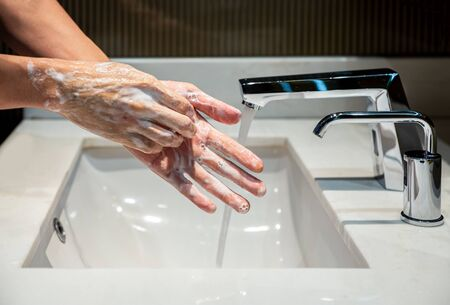 Man washing his hands with alcohol gel or soap with bubbles to sanitize and disinfect COVID-19 pathogens.