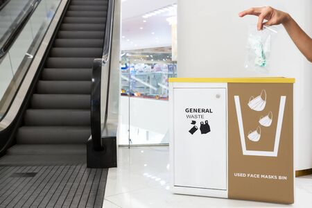 People hand throwing medical face mask covered with plastic bag into a bin at shopping mall. Right way to protect or Covid-19 concept.