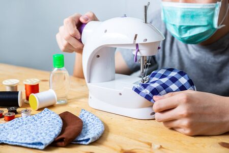 Woman sewing cloth cotton face mask to protect against the virus at home. Homemade handicraft protective mask against covid 19 virus. Reusable face mask. Zdjęcie Seryjne - 149789715