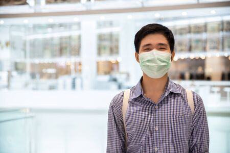 Asian man smiling behind medical protective mask in new normal lifestyle concept.