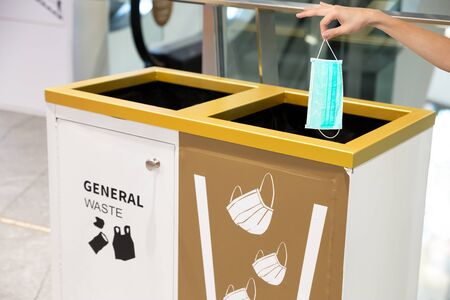People hand throwing medical face mask into a bin at shopping mall. Right way to protect or Covid-19 concept. Zdjęcie Seryjne - 149789728