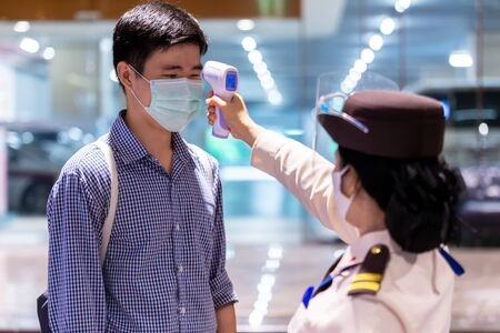 Security guard using infrared thermometer to measure body temperature check asian people in medical protective mask before access to office building for against epidemic flu Coronavirus (CoVID-19) from wuhan.