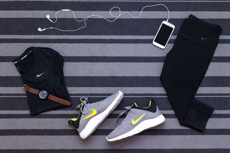 Bangkok, Thailand - August 12, 2018 : Top view of Nike KAISHI 2.0 SE Running Shoes, DRI-FIT Cool Breeze, capri crop full womens pants tights, smartphone run application isolated on grey carpet.