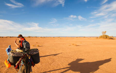 A female Tourist is riding a Camel in the Desert of Morocco Imagens