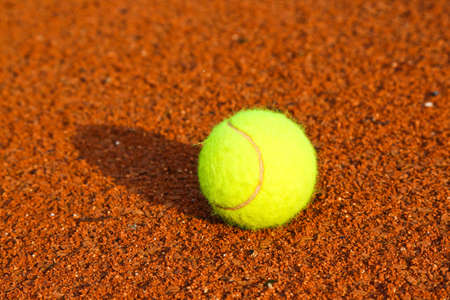 A lonely Tennis Ball on a Sand Court Imagens