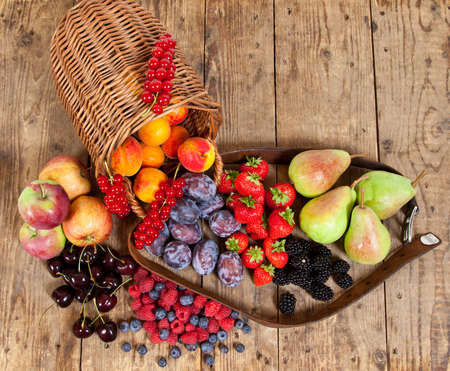 Freshly harvested seasonal Fruits, with a Basket on a wooden Table