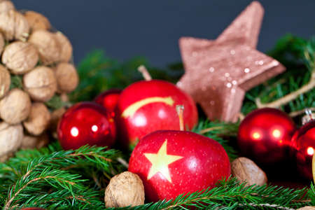 Two red Apples with a Christmas Star on it with a decoration of nuts and a star