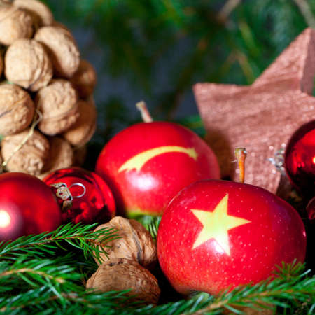Two red Apples with a Christmas Star on it on a decoration with nuts, balls and a star Imagens