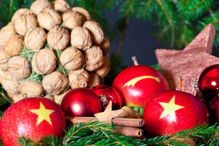 Two red Apples with a Christmas Star on it on a decoration with nuts, cinnamon and a star