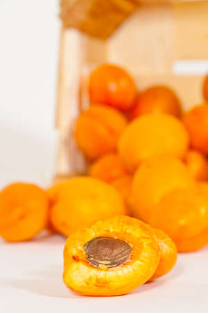 A sliced Apricot with many Apricots in the back Imagens