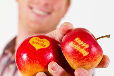 A smiling Man is holding two Happy Birthday Apples in his Hand