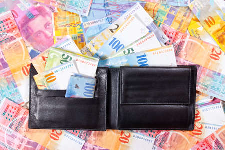 A black Wallet with Swiss Francs, is lying on a Table full of Swiss Francs