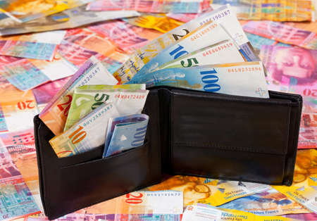 A Wallet with Swiss Francs in it, standing on a Floor with other Swiss Francs Banknotes Imagens