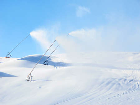 Three Snowing Machines are producing synthetic Snow in a Mountain Resort Imagens