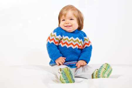 A realy happy young Kid is sitting in Studio and having Dun. Imagens