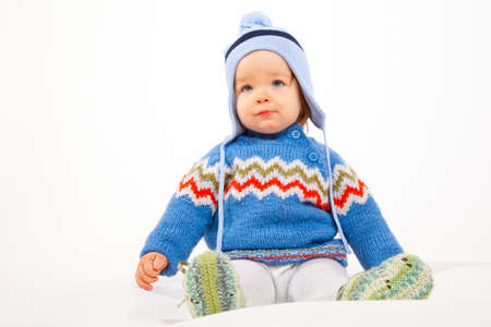 Young Kid is sitting in Studio with Winter Clothes and Hat.